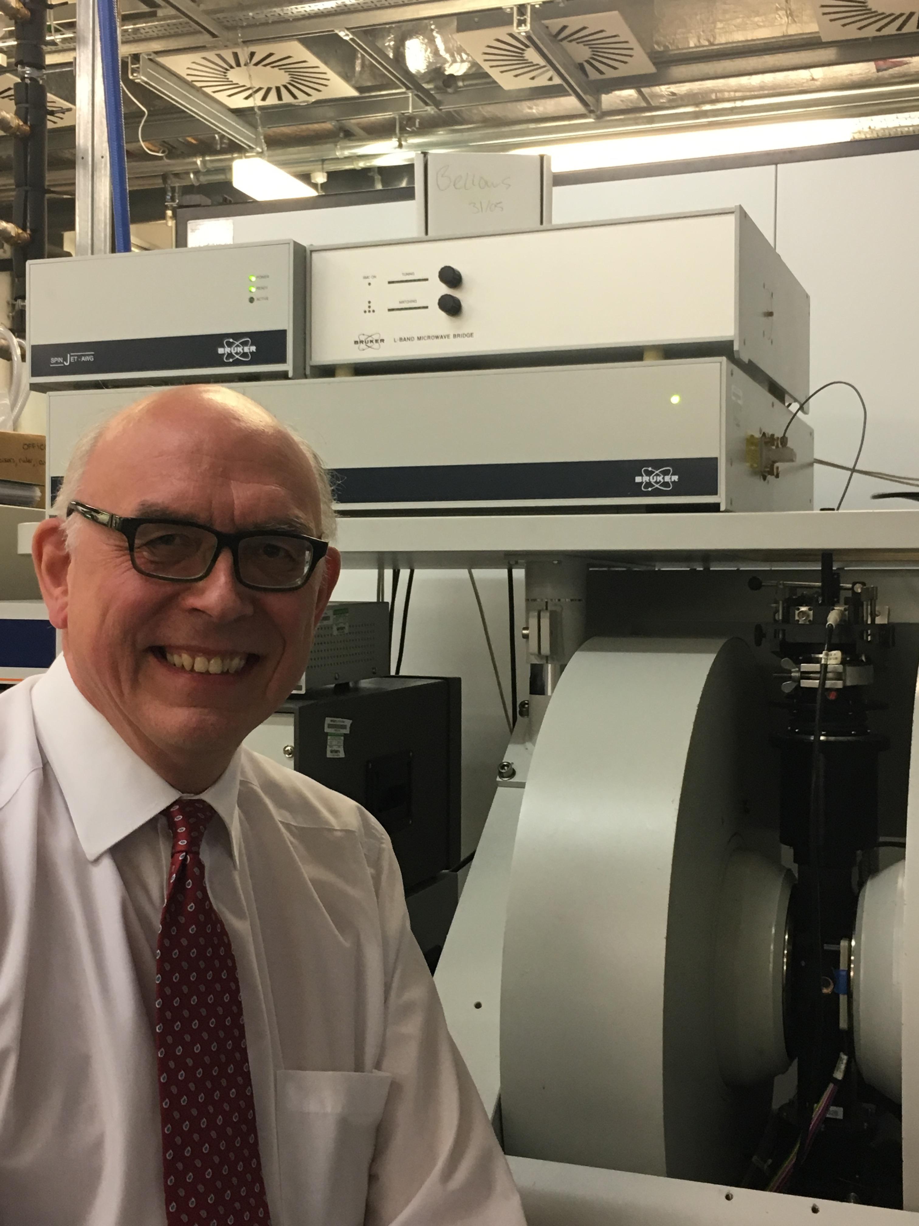 Portrait photo of Prof. David Collison with EPR spectrometer